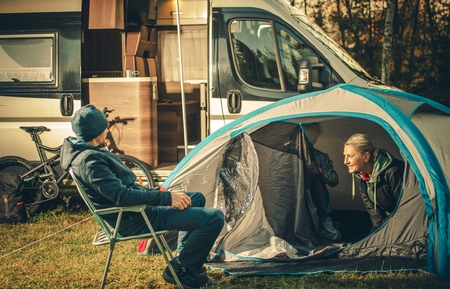 Family Camping Vacation. Motorhome and Tent on the Campsite. Caucasian Family. Stock Photo