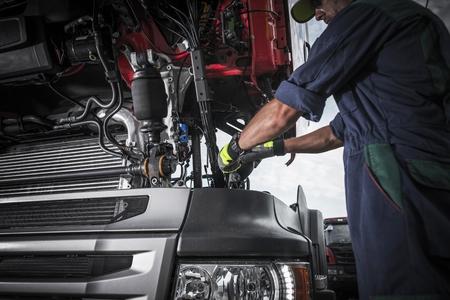 壊れた半トラック トラクター エンジンを修復しています。白人トラック メカニック。