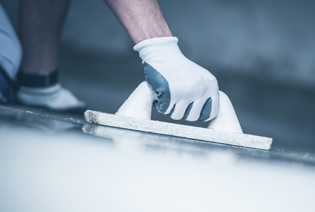 Finishing Concrete Home Floor. Closeup Photo. Hand with Finishing Tool. Construction Tool.