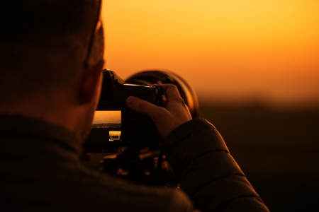 DSLR Videography and Photography Concept. Modern Digital Camera with Telephoto Lens. Photographer at Work During Scenic Sunset.