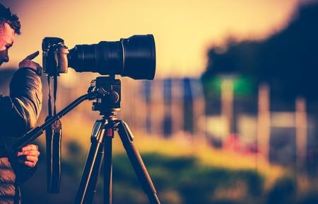 Fotógrafo profesional en el campo. Súper teleobjetivo y cámara digital en un trípode.