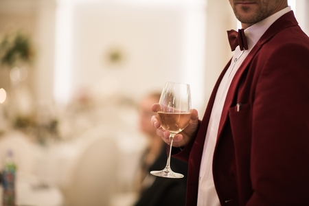 Gentleman in Burgundy Tuxedo with Glass of White Wine in Hand. Party Theme. Banco de Imagens