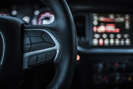 traction: Driver and the Vehicle. Driving Concept. Modern Car Steering Wheel Covered By Leather and Multimedia Dashboard in the Background.