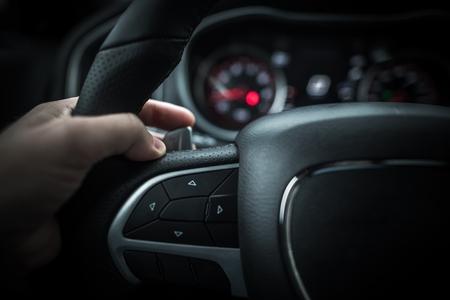 패들 이동 장치가있는 자동차 운전. 자동 변속기 기어 변경. 이동 패들에 손을 근접 촬영 사진. 스톡 콘텐츠