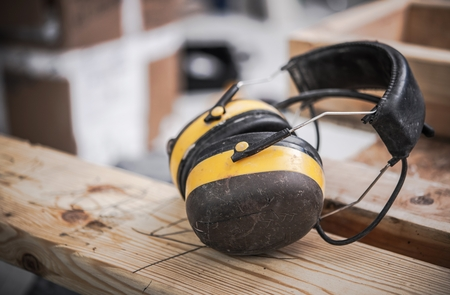 Yellow Noise Reduction Safety Ear Muffs in the Construction Site. Safety Equipment.