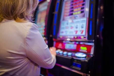 라스베가스 카지노에서 비디오 게임하는 백인 여자. 비디오 슬롯 머신. 스톡 콘텐츠