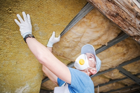 Insulating House Roof From Inside. Caucasian Contractor with Insulation Material. Stock Photo
