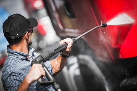 Kierowca ciężarówki myje swój ciągnik siodłowy. Motyw dla ciężarówek. Zdjęcie Seryjne
