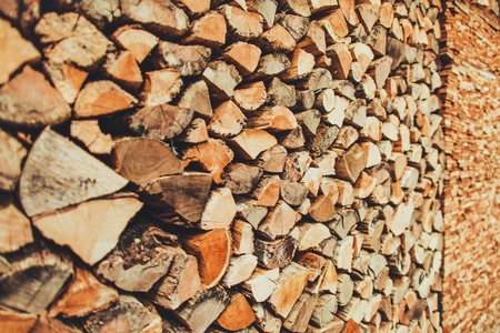 Woodshed Ready For Winter. Pile of Chopped Firewood in the Woodshed.