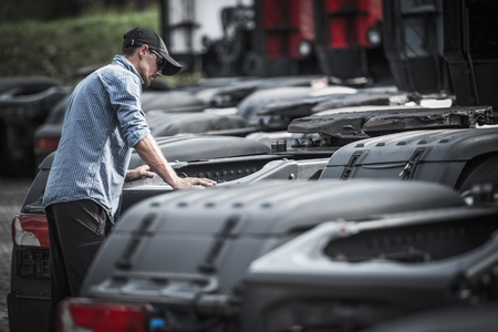Semi Truck Buyer Research. Caucasian Truck Driver Looking For New Truck For His Transportation Business.
