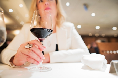 Caucasian Woman in Her 30s Enjoying Glass of Red Wine in the Restaurant.
