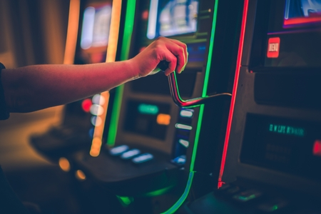 Slot Machine Play Time. Female Gambler Hand on the One Handed Bandit Slot.