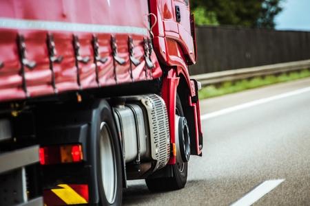 Red Speeding Semi Truck on the European Highway. Transportation Industry. Stock Photo