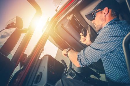 Trucker Preparing For Trip. Truck Driver Job. Caucasian Men Talking on CB Radio.