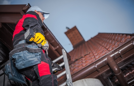 Caucasian Roof Worker with Power Tool. Residential Construction Site.  스톡 콘텐츠