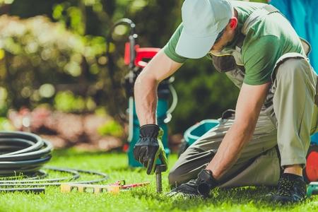 Instalação de sprinklers de campo de grama por profissional instalador de sistemas de jardim caucasiano.
