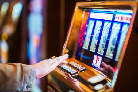 Casino Gambling Industry Theme. Caucasian Woman Playing Classic Slot Machine in the Casino. 스톡 콘텐츠