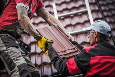 Red Roof Tiles Installatie door twee Kaukasische dakdekkers. Thema van de bouwindustrie. Stockfoto