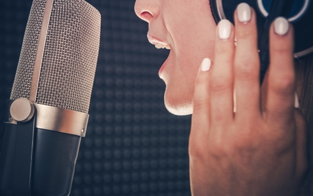 Song Recording by Singer. Professional Audio Recording in a Studio. Caucasian Female Singer with Headphones Closeup Photo. Music Industry Theme. Stock Photo