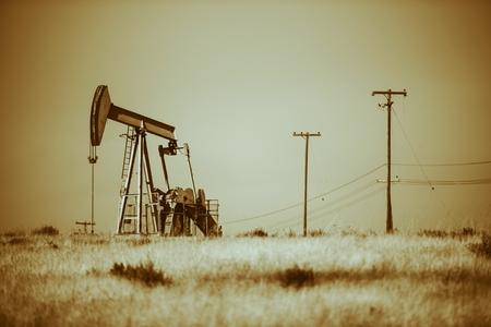 Iron Pumpjack on California Desert. Oil Industry Theme. Sepia Color Grading