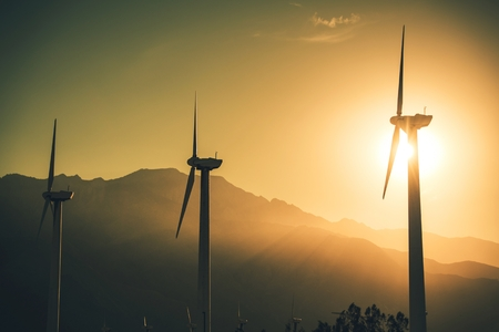 Future of Renewable Energy. Wind Turbines High Voltage Plantation at Sunset.  Stock Photo