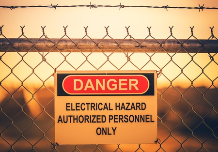 Electrical Hazard Warning Sign on Metal Fence. Authorized Personnel Only.