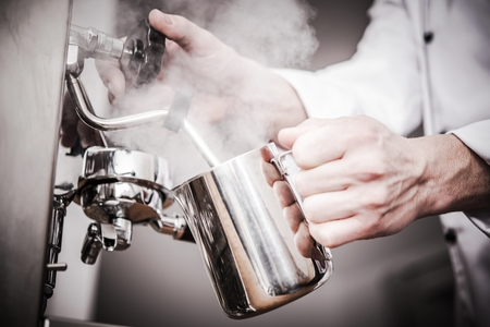Italian Barista Milk Steaming in the Stainless Steel Milk Pitcher. Closeup Photo. Preparing Fresh Espresso Based Cappuccino.