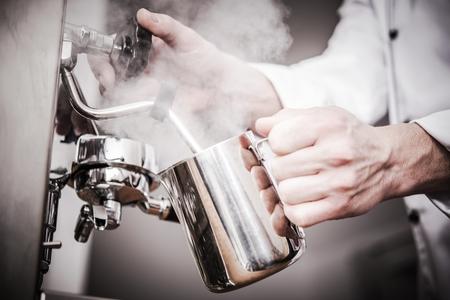 Italian Barista Milk Steaming in the Stainless Steel Milk Pitcher. Closeup Photo. Preparing Fresh Espresso Based Cappuccino.