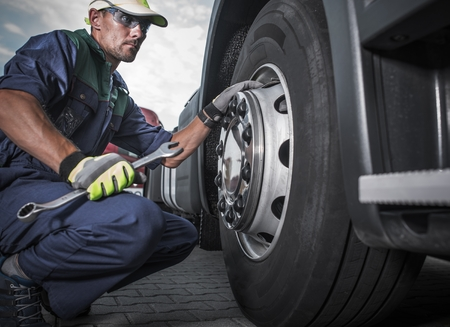 Semi Truck Wheel Maintenance. Caucasian Truck Mechanic with Large Wrench in Hand Taking Look at the Wheel in the Truck Service Center. Reklamní fotografie