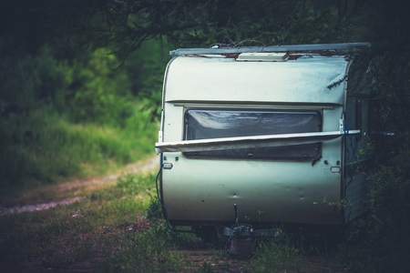 Aged and Damaged Abandoned Travel Trailer in the Middle of Nowhere. Stock Photo