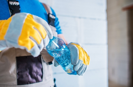 Staying Hydrated at Work. Body Hydration on the Construction Site. Caucasian Worker with Bottle of Sparkling Water. Stockfoto