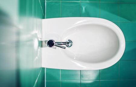 Modern Bidet Fixture Between Emerald Bathroom Tiles.