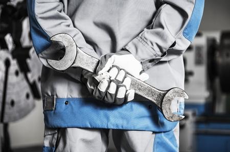 Mecânico resistente da maquinaria em um dever com a chave enorme do metal nas mãos. Foto de archivo - 94226181