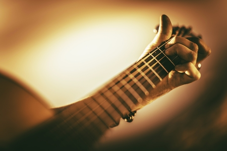 Learning Guitar Playing. Hand on a Guitar Neck Closeup Photo. Sepia Color Grading.