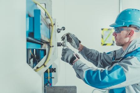 Metalworking Engineer Job. Caucasian Machine Operator Adjusting and Calibrating Metal Cutter. Фото со стока