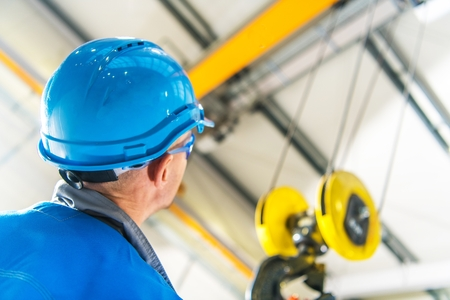 Caucasian Production Line Technician in Blue Hard Hat Checking on the Overhead Warehouse Crane Installed Right Above His Head 스톡 콘텐츠