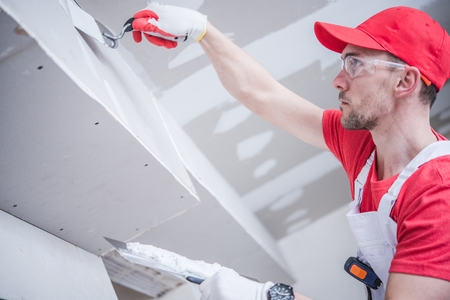 Residential Remodeling Drywall Patching. Caucasian Contractor in His 30s. Construction Theme. Stock Photo
