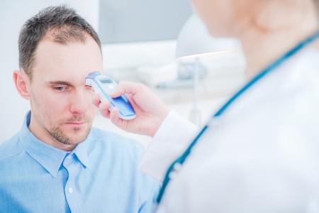Körpertemperaturmessung. Ärztin prüft die Temperatur mit einem Infrarot-Thermometer