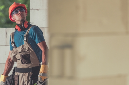Caucasian Construction Site Builder Contractor Between Raw Walls of Newly Developed Building. Reklamní fotografie