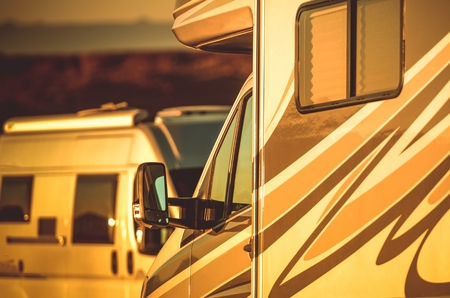 Camper Vans Camping. Motorhomes Camper Vans in the RV Park During Sunset. Closeup Photo. Stock Photo