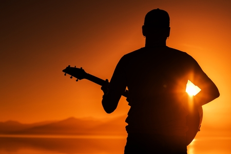 Guitar Playing at Sunset. Men with Acoustic Guitar During Scenic Sunset. String Instrument Theme Reklamní fotografie