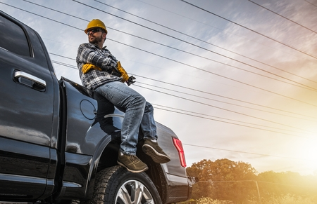 Caucasian Construction Worker Relaxing on His Pickup Truck. Freelance Handyman Worker Stock Photo