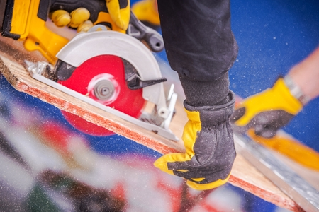Construction and Remodeling Theme. Worker Cutting Plywood Using Circular Saw. Closeup  Photo
