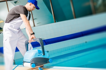 Swimming Pool Technician with Automated Pool Cleaner Preparing For Cleaning.