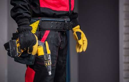Worker with Power Tool Preparing For Work. Closeup Photo. Construction Theme.