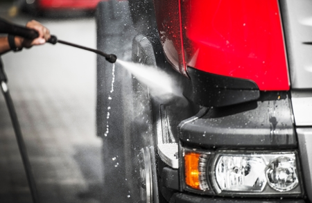 Caucasian Driver Washing His Truck Using High Pressure Cleaner. Reklamní fotografie - 97235948