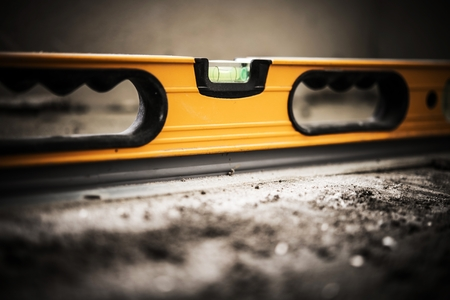Construction Spirit Level Tool Instrument on the Raw Concrete Floor. Closeup Photo.