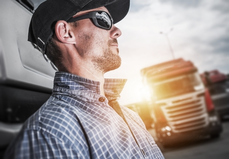 Proud Caucasian Semi Truck Driver Portrait In Front of His Truck.