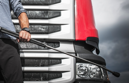 Manual Truck Washing Using High Pressure Cleaner. Taking Care of Truck Concept with Caucasian Driver. Reklamní fotografie