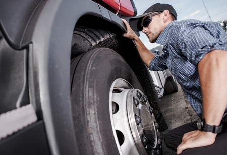 Caucasian Truck Driver Making Quick Tires Check. Transportation Industry.